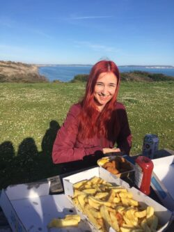 Alfiia is sat at a picnic bench eating fish and chips in the field close to Highcliffe Beach. The sky is blue and you can see the ocean behind her on the horizon.