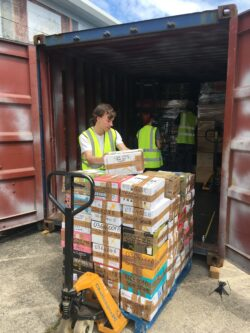 Volunteers Oleg and Alfiia are helping workshop manager Stuart to load the container with a pallet of cardboard boxes filled with haberdashery kits