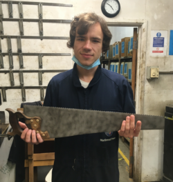 Oleg is stood in the workshop facing the camera holding a large saw he has recently refurbished.