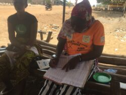 Two women from their local VSLA (village savings loan association) sit on a bench in the shade with one woman recording the recent saving contribution from the group in an exercise book
