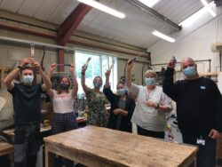 Six people are stood next to each other in a line inside the Tools for Self Reliance workshop wearing masks and holding up hand tools donated from Draper Tools