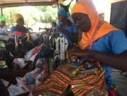 Three women sat at sewing machines making clothes with bright coloured fabric.