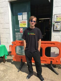 Oleg is standing up and facing forward to the camera wearing his black Tools for Self Reliance t-shirt, black trousers and sunglasses in front of the workshop back door. There is a also a plastic orange barrier behind him.