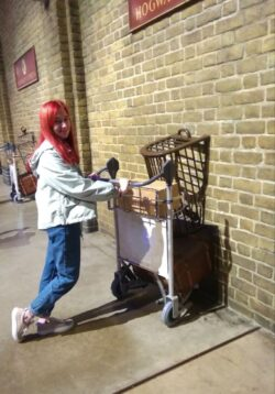 Alfiia is standing and pushing a luggage trolley into the wall at The Harry Potter Platform 9 three quarters at Kings Cross in London. She has red hair past her shoulders and is wearing blue jeans, white trainers and a grey jacket
