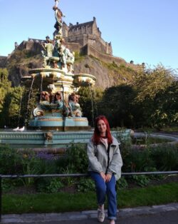 Alfiia is sat on the railing infront of the The Ross Fountain, an ornate fountain in the city of Edinburgh. In the background is Edinburgh Castle. She is wearing a light grey jacket and blue jeans.
